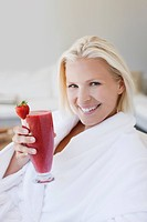 Woman in bathrobe drinking fruit smoothie
