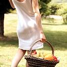 particolare una donna con un cesto di verdura in un giardino