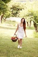 una donna con un cesto di verdura in un giardino
