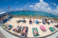 Tourists sunning on beach chairs on the waterfront in Georgetown on Grand Cayman in the Cayman Islands with cruise ships in the caribbean sea off shor...