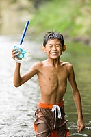 Boy standing in river holding snorkel, Chiba Prefecture, Honshu, Japan