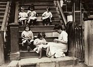 HINE: HOME INDUSTRY, 1912.A woman with a group of young girls working on garment tags on a tenement stoop in Roxbury, Massachusetts. Photograph by Lew...