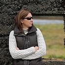 Casual portrait woman in sunglasses, down vest, and knit sweater , before rugged stone window frame