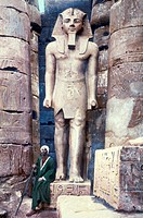 EGYPT: LUXOR TEMPLE.A man seated next to a statue of Pharaoh Ramesses II at the Luxor Temple. Undated hand-colored photograph.