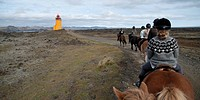 Horse ride on a path towards a lighthouse