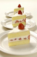 Plates of sliced strawberry cakes, white background