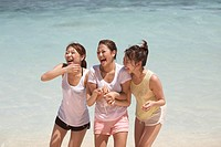 Young women holding hands in water, Guam, USA