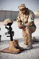 A soldier bows to pay tribute to a fallen soldier.