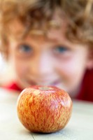 Close_up of an apple with a boy in the background