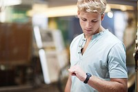 Young man checking the time in a clothing store