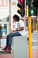 Man using a laptop near traffic light (thumbnail)