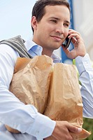 Mid adult man talking on a mobile phone with paper bags full of vegetables