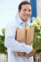 Portrait of a mid adult man holding paper bags full of vegetables and smiling