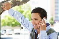 Close_up of a mid adult man holding a branch of tree talking on a mobile phone
