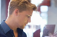 Side profile of a young man doing window shopping