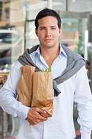 Portrait of a mid adult man holding paper bags full of vegetables
