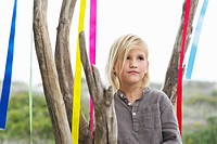 Girl standing near a tree decorated with ribbon