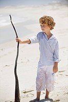 Boy holding a wooden stick on the beach