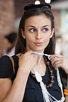 Young woman trying a necklace in a mall