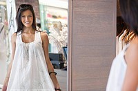 Portrait of a beautiful young woman trying on a dress in a mirror (thumbnail)