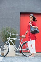 Portrait of a young woman standing with a bicycle (thumbnail)