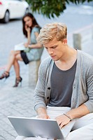 Young man using a laptop with a woman in the background on a street