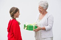 Senior woman giving gift to her granddaughter