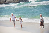 Senior couple enjoying on the beach with their granddaughter