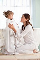 Woman wrapping her daughter in towel after the bath