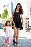 Portrait of a beautiful young woman with her cute little daughter walking
