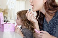 Young woman and little girl applying make_up at dressing table