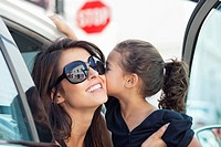 Beautiful young woman with her cute little daughter kissing in a car
