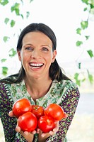 Portrait of a smiling mature woman holding tomatoes