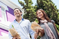 Smiling couple standing with paper bags full of vegetables