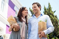 Smiling couple looking at each other with paper bags full of vegetables