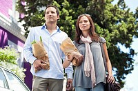 Couple standing with paper bags full of vegetables