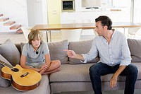 Father complaining to teenage boy sitting with guitar at home (thumbnail)