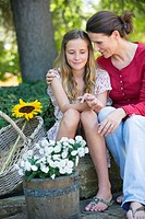 Little girl and mother sitting outdoors with flowers in the basket