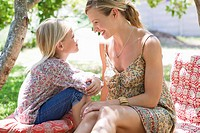 Side profile of mother and a little girl looking to each other outdoors