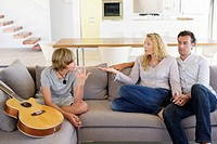Teenage boy talking to his mother on a couch