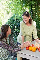 Senior woman talking to her daughter with vegetables on table