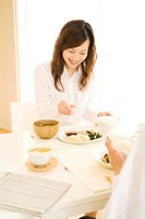 Woman sitting eating breakfast