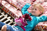 Portrait of a little girl lying in hammock with a toy