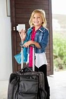 Girl with luggage at the door waving her hand