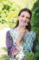 Portrait of a smiling mature woman smelling flowers in garden