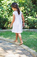 Rear view of a little girl walking in the garden