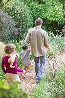Father with two children walking in a garden