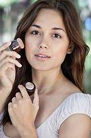 Portrait of a beautiful young woman applying make_up