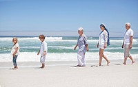 Family walking in a row along the beach with kids