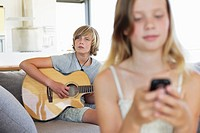 Teenage boy playing a guitar while his sister using a mobile phone